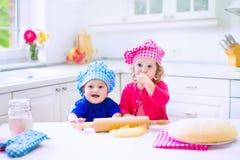 Enfants faisant cuire au four dans une cuisine blanche Image stock