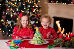 Enfants faisant cuire au four le réveillon de Noël Photographie stock