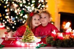 Enfants faisant cuire au four le réveillon de Noël Photos libres de droits