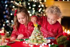Enfants faisant cuire au four le réveillon de Noël Photos stock