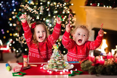 Enfants faisant cuire au four le réveillon de Noël Photo stock