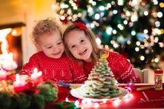 Enfants faisant cuire au four le réveillon de Noël Images stock