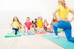 Enfants faisant des exercices avec l'entraîneur féminin de gymnastique photos stock