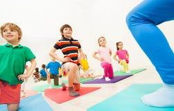 Enfants faisant des exercices de recourbement de genou à la leçon de gymnase Photos stock
