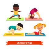 Enfants faisant des poses de yoga sur les tapis colorés Image libre de droits