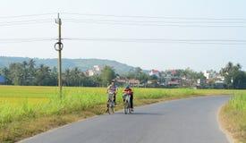 Enfants faisant du vélo sur la route rurale dans Phuyen, Vietnam Photos libres de droits