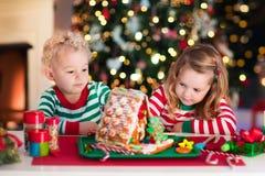 Enfants faisant la maison de pain de gingembre de Noël Photos stock