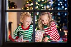 Enfants faisant la maison de pain de gingembre de Noël Photo stock