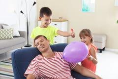 Enfants faisant la plaisanterie d'explosion de ballon pour leur père photos libres de droits