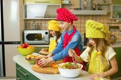 Enfants faisant la salade, cuisine Photographie stock