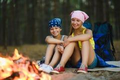 Enfants fatigués et heureux s'asseyant au feu de camp Image stock