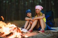 Enfants fatigués et heureux s'asseyant au feu de camp Photographie stock