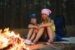 Enfants fatigués et heureux s'asseyant au feu de camp Photographie stock libre de droits