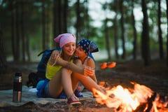 Enfants fatigués et heureux s'asseyant au feu de camp et aux saucisses frites Images stock