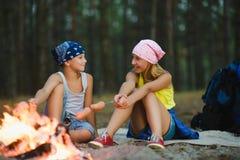 Enfants fatigués et heureux s'asseyant au feu de camp et aux saucisses frites Photo stock