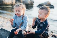 Enfants, fille et gar?on mangeant la tomate et le concombre sur le fond de mer photos libres de droits