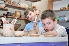 Enfants formant l'argile dans le studio de poterie Images libres de droits