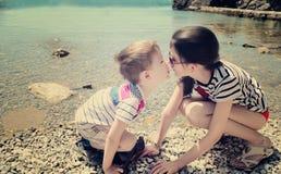 Enfants frère et baiser de soeur sur la plage modifiant la tonalité l'EFF de vanille Photos stock