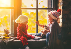Enfants frère et fenêtre admirative de soeur pour l'automne photographie stock libre de droits