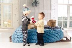 Enfants frère et soeur se tenant et jouant à la maison dans la chambre à coucher près du lit avec les boîtes, cadeaux sur le fond images stock