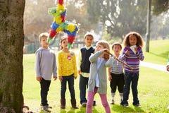 Enfants frappant le Pinata à la fête d'anniversaire Images libres de droits
