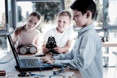 Enfants futés collaborant au-dessus des machines robotiques Photos stock