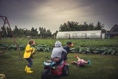 Enfants gais ayant le terrain de jeu d'amusement dehors pendant des vacances d'été dans la campagne symbolisant l'enfance insouci Photographie stock