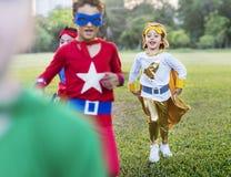 Enfants gais de super héros exprimant le concept de positivité Photographie stock