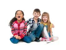 Enfants gais de Thre s'asseyant sur le plancher dans un studio Photo stock