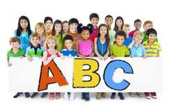 Enfants gais divers tenant des lettres Images libres de droits