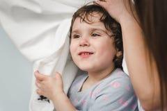 Enfants gais et parents ayant le combat d'oreiller sur le lit à la maison photo libre de droits