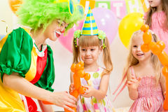 Enfants gais groupe et clown sur la fête d'anniversaire Photo stock