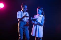 Enfants gais jouant avec leur comprimé Photographie stock