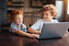 Enfants gais jouant sur l'ordinateur portable ensemble Images stock