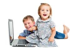 Enfants gais, s'asseyant devant l'ordinateur portable Images libres de droits