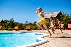 Enfants gais se réjouissant, sauter, nageant dans la piscine Image libre de droits