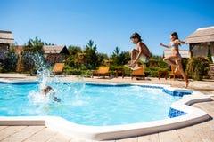 Enfants gais se réjouissant, sauter, nageant dans la piscine Photos libres de droits