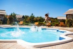 Enfants gais se réjouissant, sauter, nageant dans la piscine Image stock