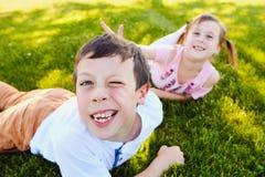 Enfants gais se trouvant sur l'herbe et faisant l'amusement Images stock