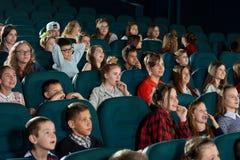 Enfants gais souriant et observant la bande dessinée dans le théâtre de film Images stock
