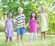 Enfants gais tenant des mains en parc Images stock