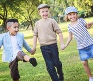 Enfants gais tenant des mains en parc Photo libre de droits