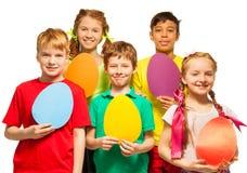 Enfants gais tenant les cartes colorées de forme d'oeufs Images stock
