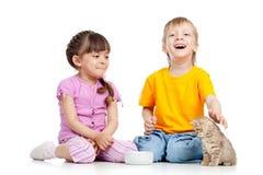 Enfants garçon et fille alimentant le chaton attrayant Photos libres de droits