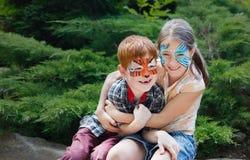 Enfants, garçon et fille heureux avec la peinture de visage en parc Images stock