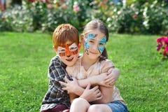 Enfants, garçon et fille heureux avec la peinture de visage en parc Photo stock