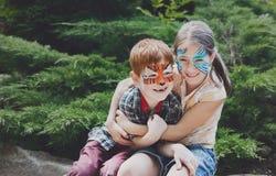 Enfants, garçon et fille heureux avec la peinture de visage en parc Image stock