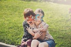 Enfants, garçon et fille heureux avec la peinture de visage en parc Photos libres de droits