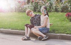 Enfants, garçon et fille heureux avec la peinture de visage en parc Images libres de droits