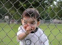 Enfants : Garçon scrutant par la frontière de sécurité Images libres de droits